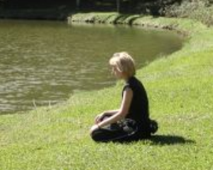 woman in meditation by lake