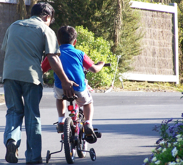 parent helping child learn to ride a bike